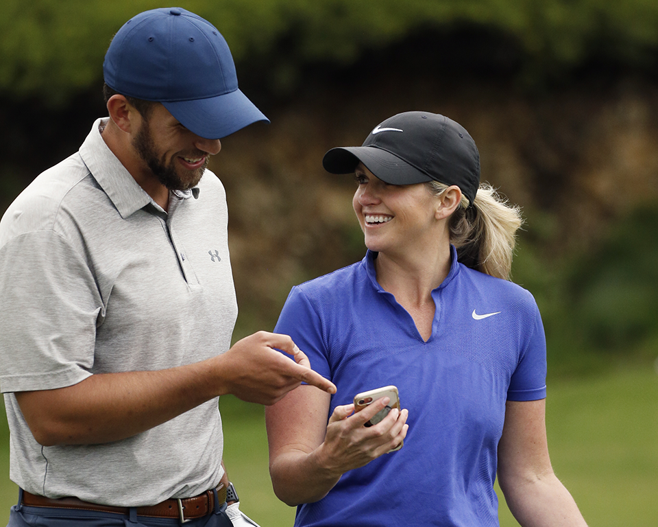 A man and a women talking on the golf course