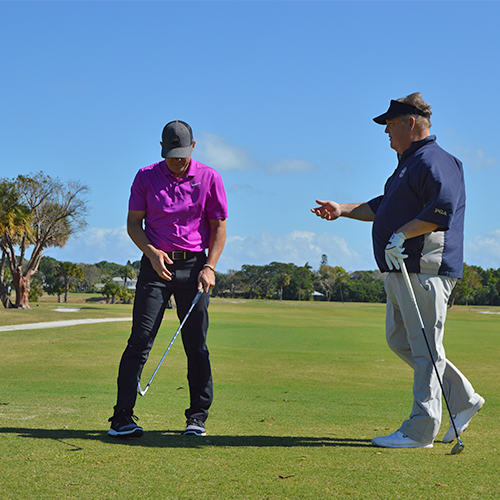 An instructor speaking with a golfer