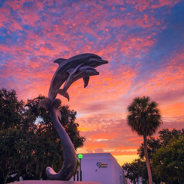 A statue of jumping dolphins and a pink sunset