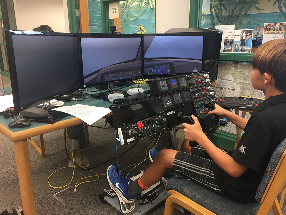 Picture of a teen using the flight simulator at the Morgade library