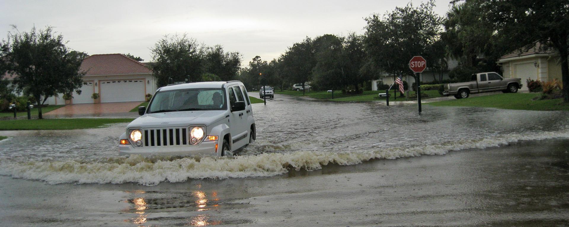 An SUV driving through a flooded neighborhood