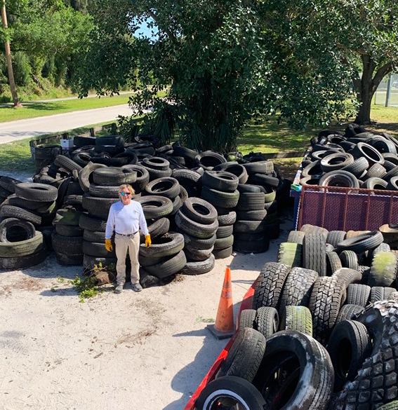 A man standing in front of hundreds of tires to be recycled