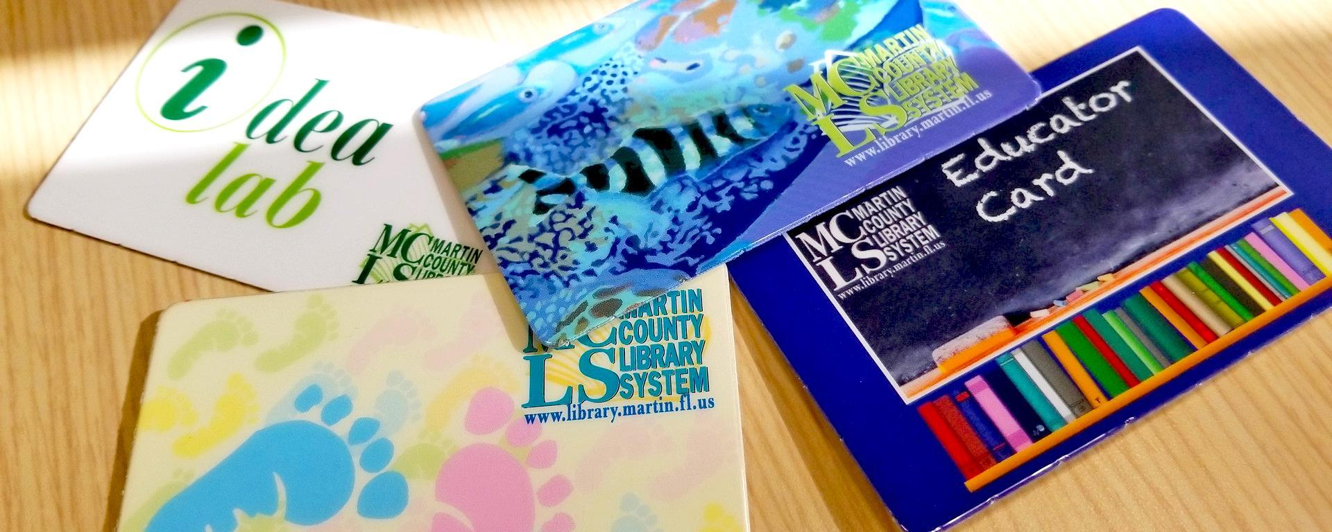 Image of four types of martin county library cards. The classic card, educator card, idea lab card, and baby card.