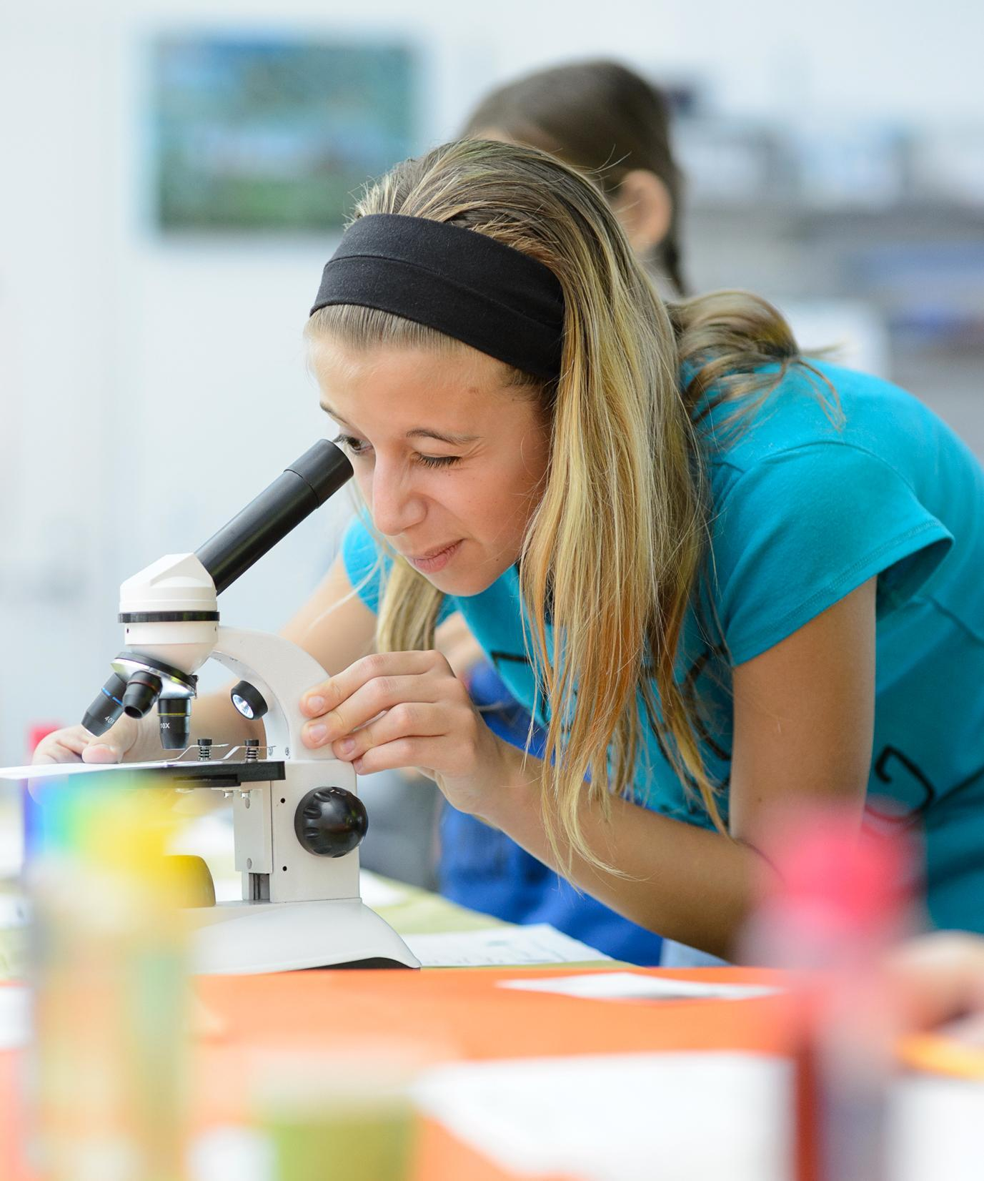 pircure of a teenage girl looking through a microscope during a library event