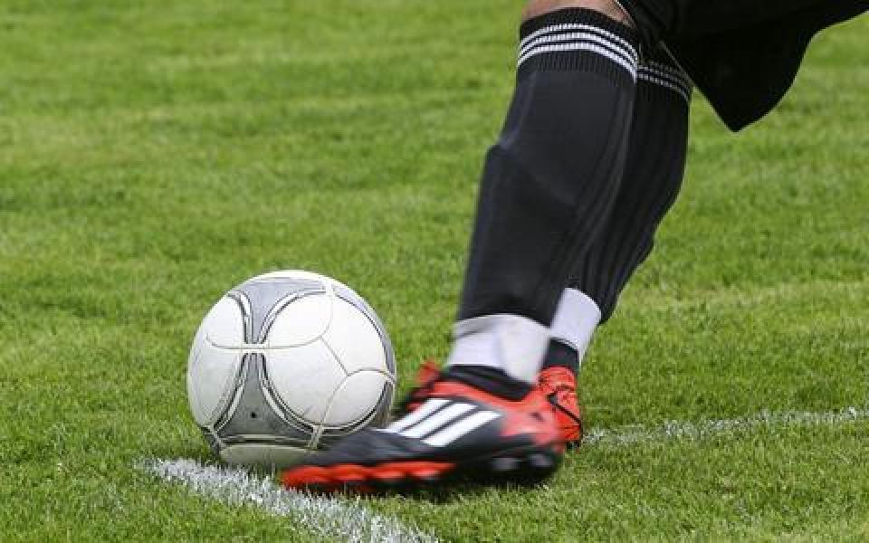 A foot kicking a soccer ball
