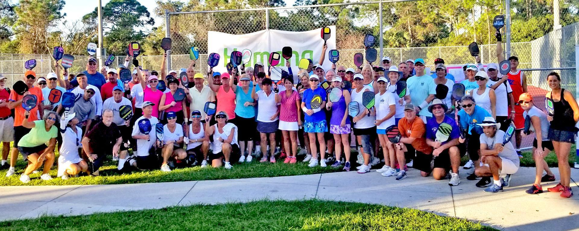 a group of senior games participants holding pickleball rackets