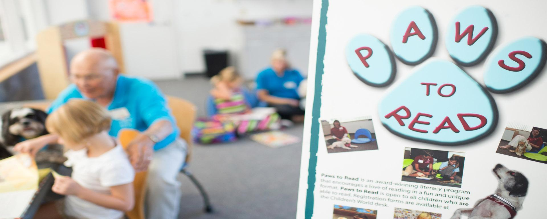 Image of the children reading to dogs during paws to read