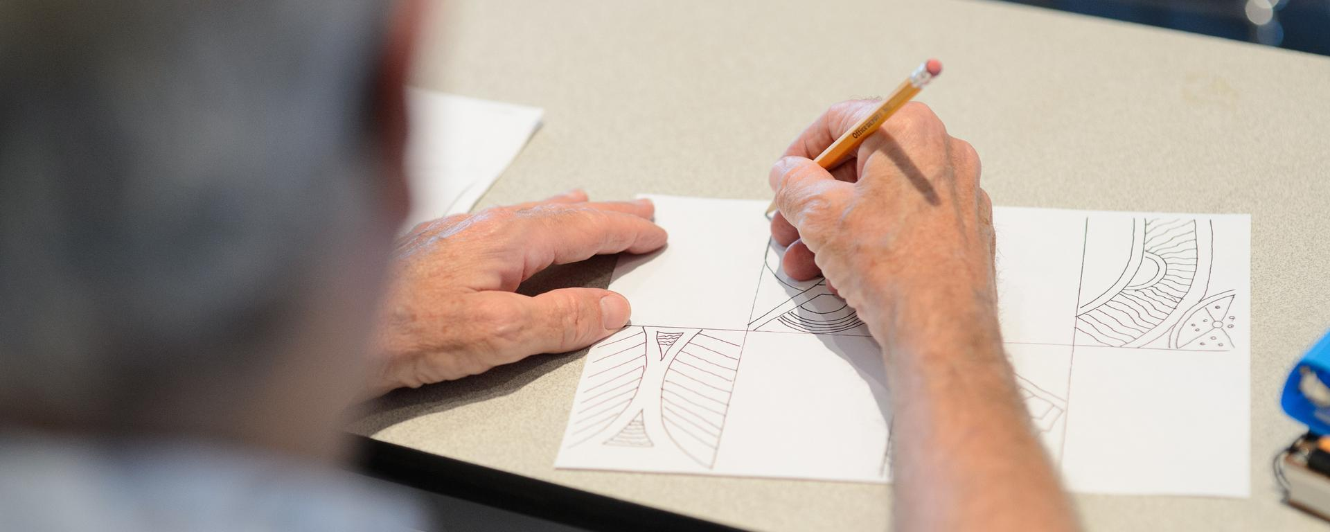 hands drawing a picture at a free library event