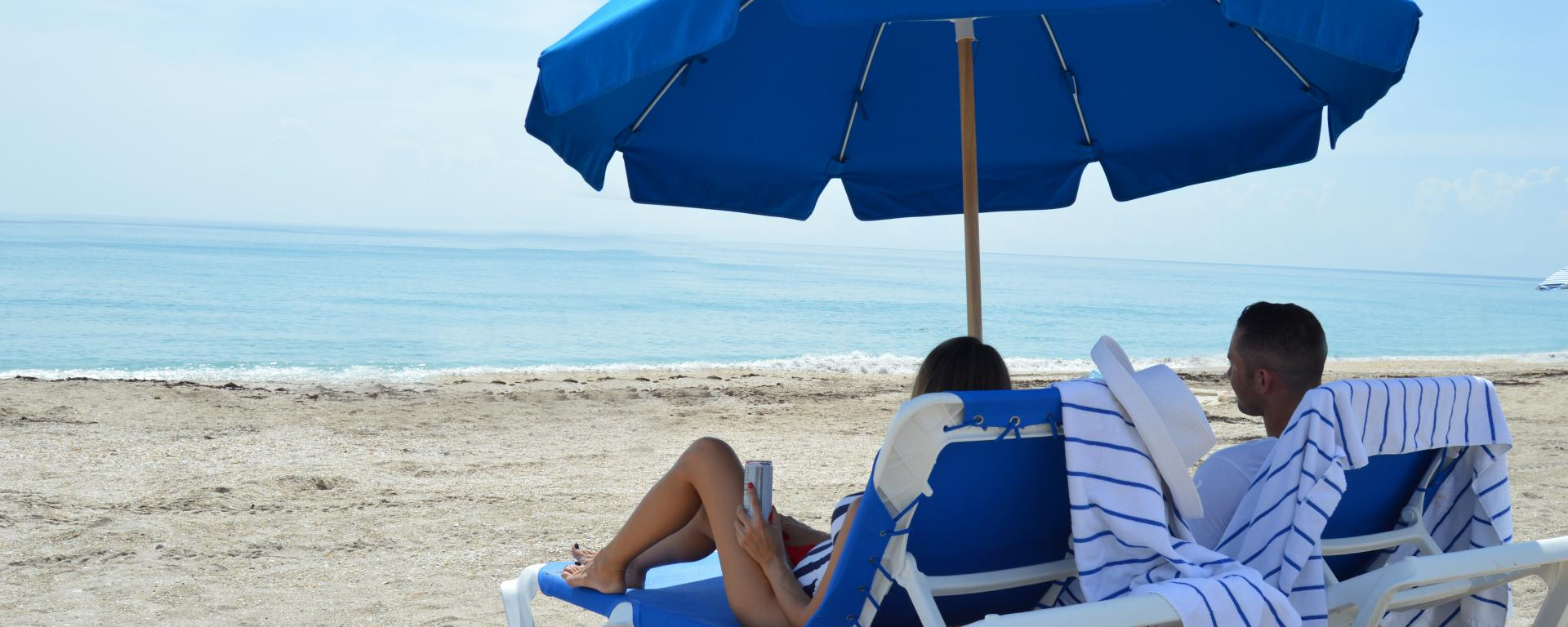 A couple sitting on the beach in beach chairs and an umbrella.
