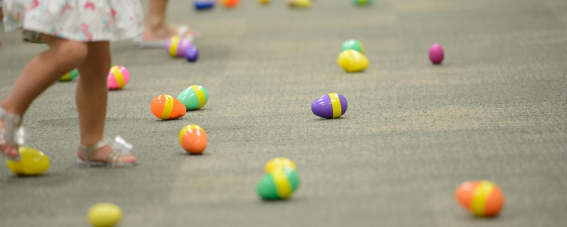 plastic eggs on the floor and a childs legs