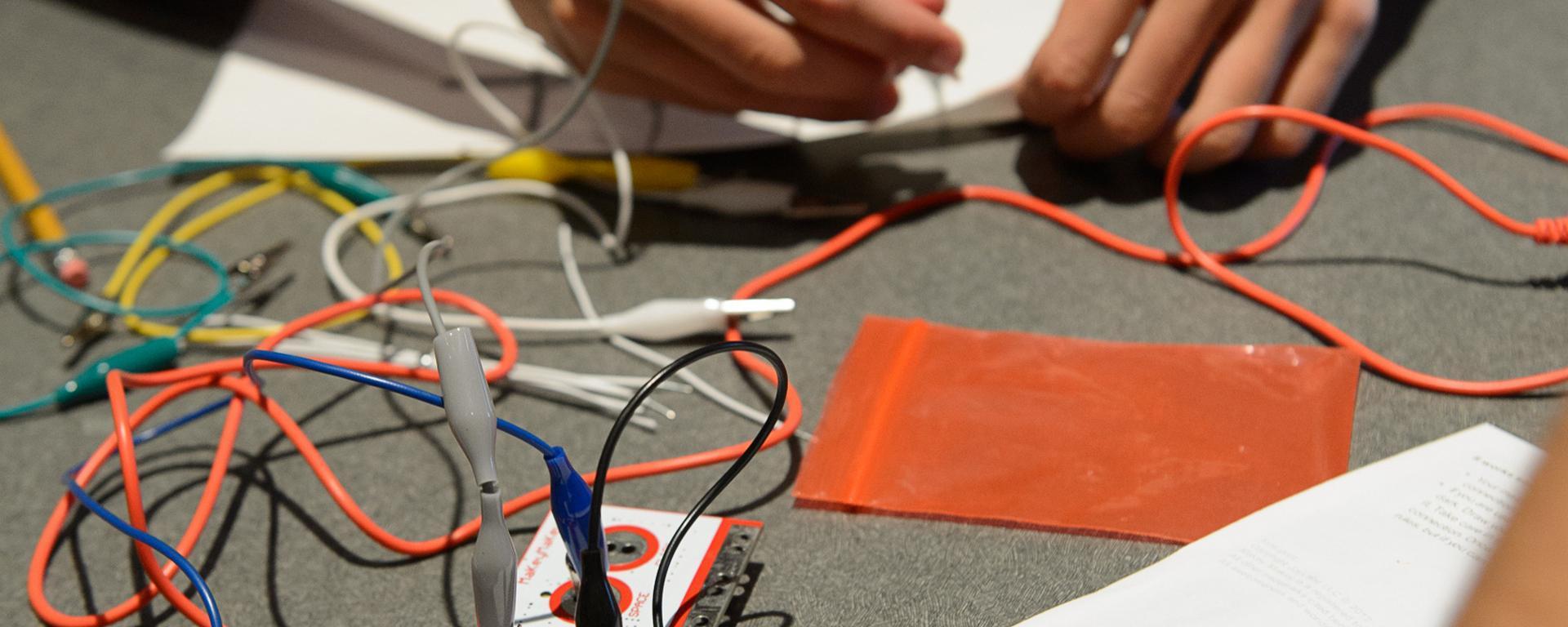 teens using a makey-makey circuit board