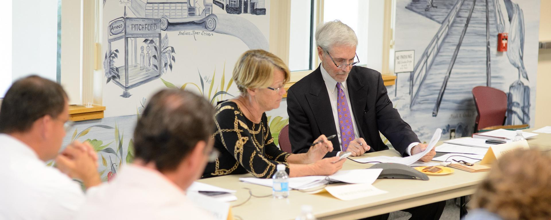 Image focusing on two people at a business meeting reviewing a report
