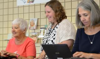staff helping a patron use a laptop