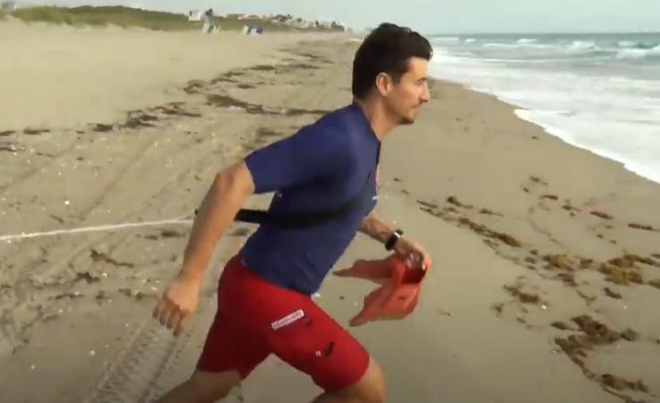 A lifeguard running towards the water