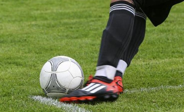 A foot kicking a soccer ball