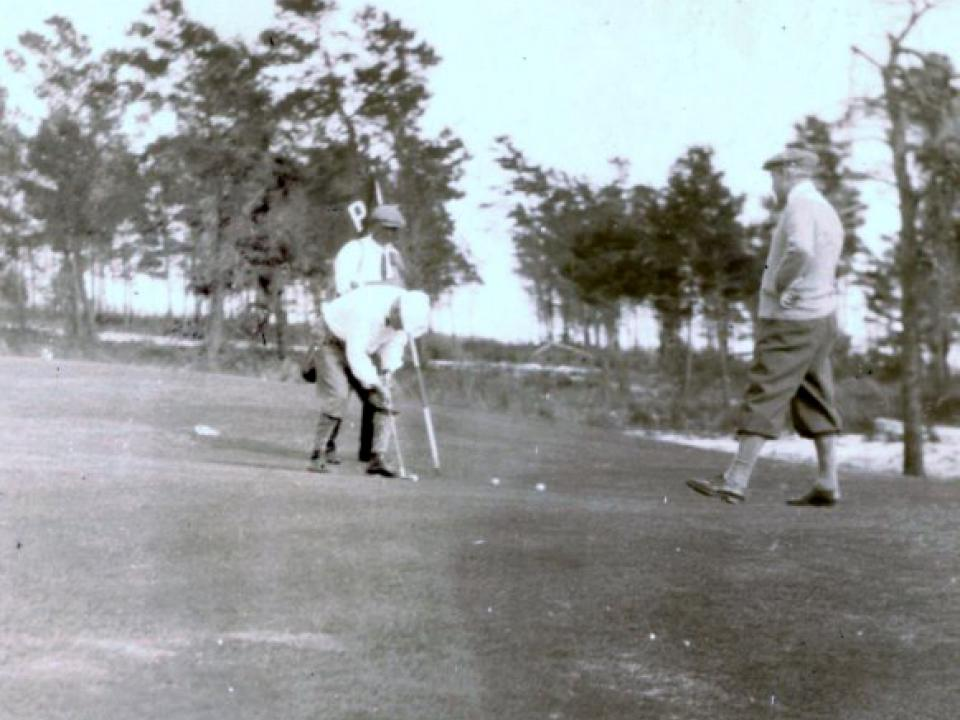 Golf course historical photo showing two men playing golf