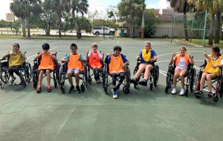 Teens posing for a photo after a wheelchair basketball game.