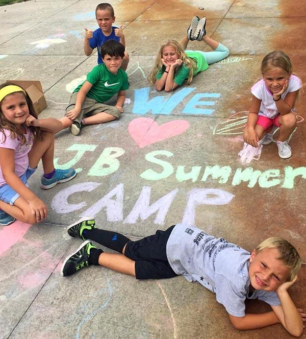 Kids playing with sidewalk chalk during summer camp activities