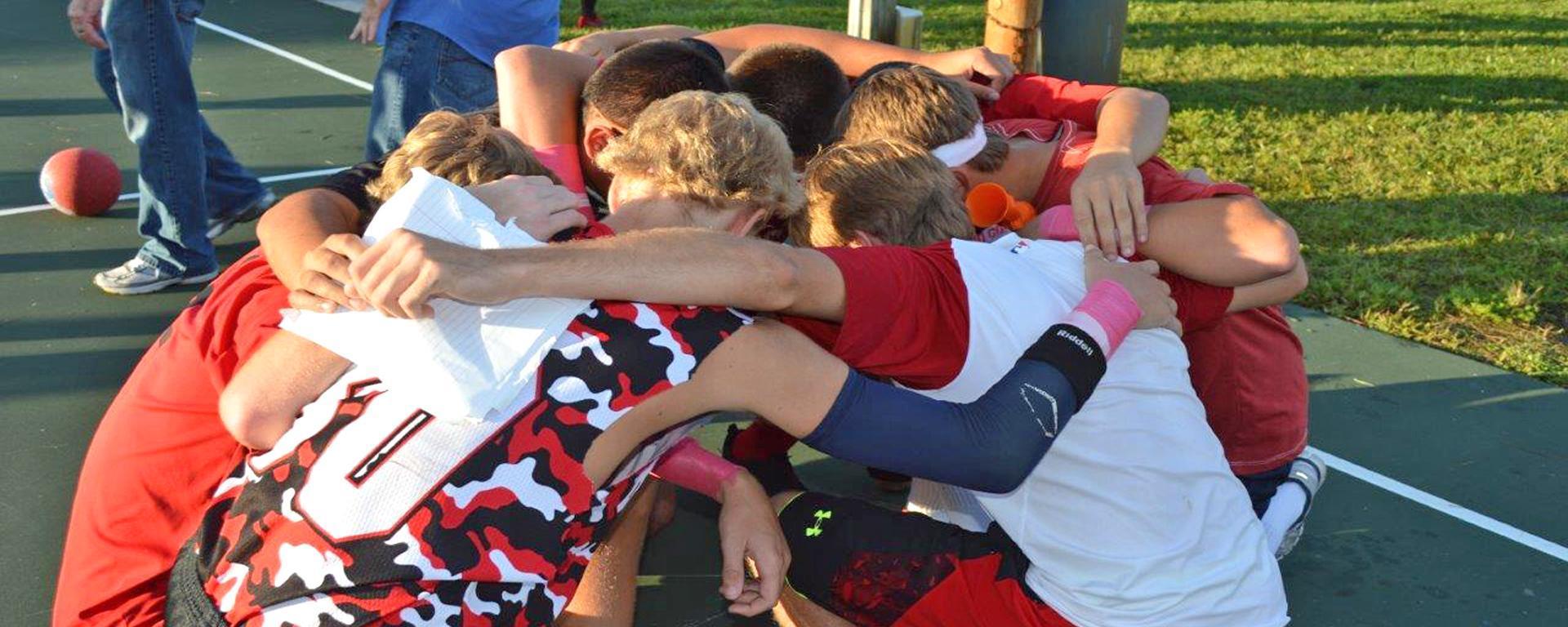 Teens huddle during a dodgeball tournament.