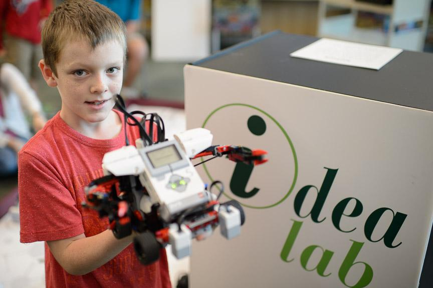 Picture of a young boy proudly displaying a robot he made in an idea lab